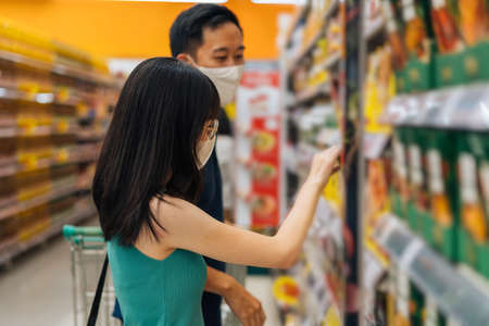 Foto für Woman and man shopping in grocery store wearing protective face coverings, choosing food in supermarket aisle, looking at products, grocery shopping during the pandemic - Lizenzfreies Bild