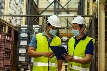 Photo pour Group of young factory warehouse workers wearing a protective face mask while working in logistic industry indoor. Asian and Indian ethnic men checking item order during Coronavirus Covid 19 pandemic - image libre de droit