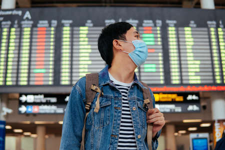 Foto für Asian male traveler wearing a face mask waiting for boarding airplane. Young tourist waiting in airport with departure board in background during Covid-19 virus pandemic - Lizenzfreies Bild