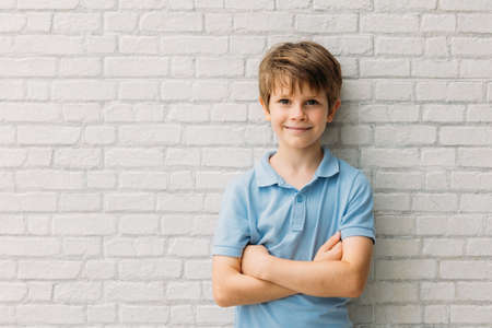 Photo pour Portrait of happy young caucasian boy in casual outfit with arms crossed isolated over white bricks background smiling and looking at camera - image libre de droit