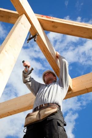 Foto de construction worker at work with wooden  roof construction - Imagen libre de derechos