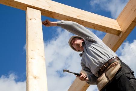 Photo pour construction worker at work with wooden  roof construction - image libre de droit