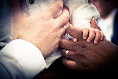 Photo pour Close-up of hands Interracial couple holding their child. Vintage look with vignette. Focus on the center - image libre de droit