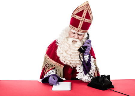 Photo pour Sinterklaas with old telephone Vintage look isolated on white background Dutch character of Santa Claus - image libre de droit