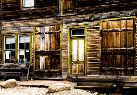 Wooden storefront of an old mining ghost town that is weathered.