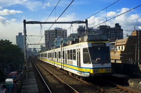 Manila, Philippines - April 02, 2012: LRT train arrives at a train station. LRT serves 579,000 passengers each day. Its 31 stations along over 31 kilometers (19 mi) of mostly elevated track form two lines