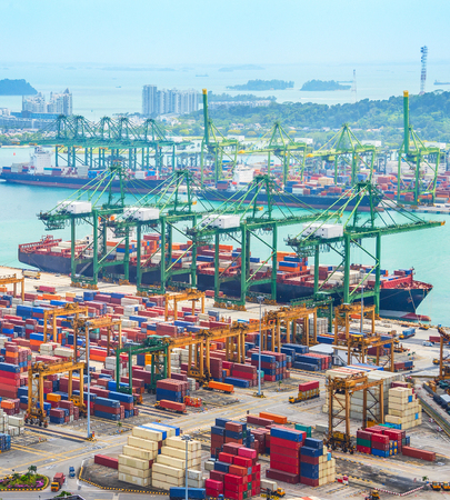 Photo for Aerial view of cargo ships in Singapore industrial port harbor by pier with freight cranes and goods containers, seacsape at background - Royalty Free Image