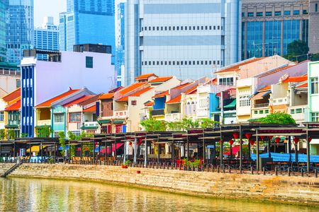 Photo for Cityscape with colorful bars, restaurants and stores by the Singapore River along Boat Quay, skyscrapers of modern architecture in background - Royalty Free Image
