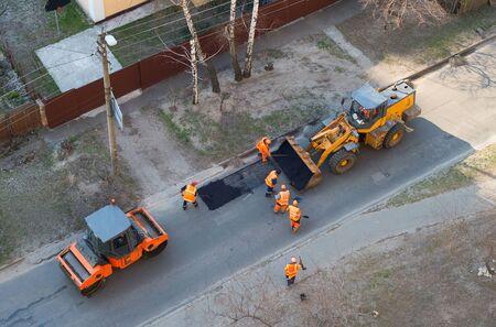 Photo pour Workers, excavator, roller compactor repair road, top view, Kiev, Ukraine - image libre de droit