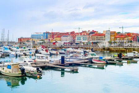 Photo for Overcast citycsape with yachts and motor boats moored by piers in marina, Gijon, Asturias, Spain - Royalty Free Image