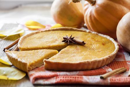 Foto de Homemade spicy pumpkin pie with cinnamon on a table with pumkings at background - Imagen libre de derechos