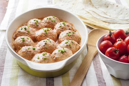 Photo pour Homemade chicken meatballs baked in creamy tomato sauce in ceramic baking dish - image libre de droit