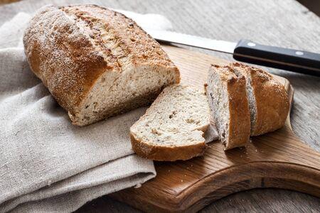 Foto für Loaf of whole wheat bread with slices on wooden board on kitchen table - Lizenzfreies Bild