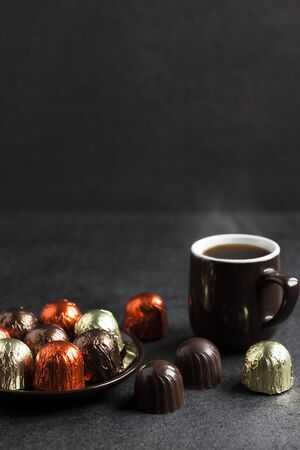 Photo pour Chocolate candies wrapped in multicolored foil on a plate and cup of hot coffee on black background with copy space - image libre de droit