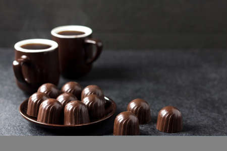 Photo pour Chocolate candies on a plate and two cups of hot coffee on black background with copy space - image libre de droit