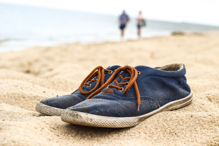 Simple blue men shoes with brown laces on sand on beach. Two people walking in the background