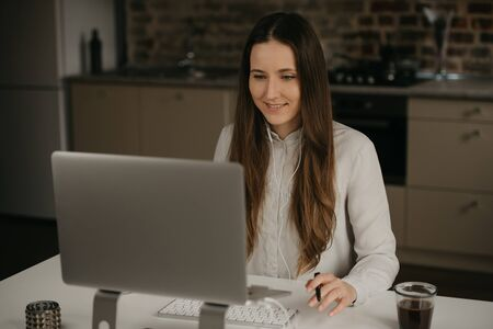 Photo pour Remote work. A caucasian brunette woman with headphones working remotely on her laptop. A happy girl in a white shirt doing business at her home workplace. - image libre de droit