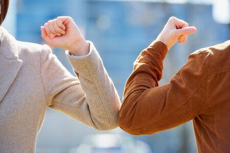 Foto de A close-up photo of elbow bumping. Elbow greeting to avoid the spread of coronavirus (COVID-19). A man and a woman meet with bare hands. Instead of greeting with a hug or handshake, they bump elbows. - Imagen libre de derechos