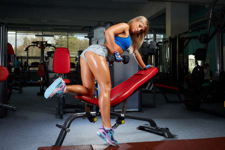 Photo pour A sporty blond girl who wears denim shorts and a blue tight tank top is doing a single-arm dumbbell row on a red bench in a gym. A female coach is pulling a dumbbell. - image libre de droit