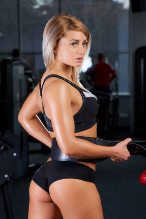 Photo for A sporty young woman who wears black tight shorts and a tank top is tightening a leather weight lifting belt. A fitness blond girl is posing with her back in a gym. - Royalty Free Image