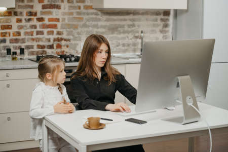 Photo for A mother is working remotely at home while a daughter is watching it. A businesswoman is working from an apartment near her blonde child. - Royalty Free Image