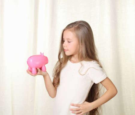 Littlr blond girl looking on piggy moneybox