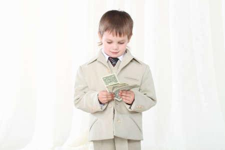 Photo pour Little smart boy in suit showing dollars - image libre de droit