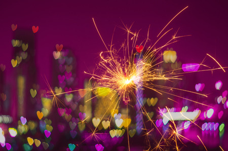 Electric sparklers with heart bokeh background