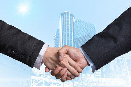 Photo for Hand shake between a businessman on Modern business building glass area background - Royalty Free Image