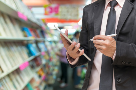 Businessman using the tablet on Abstract blurred photo of book store background