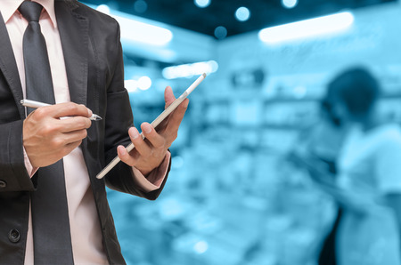 Businessman using the tablet on on Abstract blurred photo of book store with people background