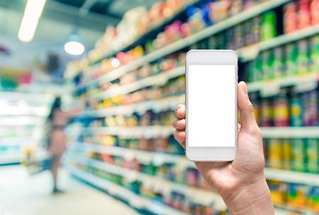Photo pour Female hand holding mobile smart phone on Supermarket blur background, business concept - image libre de droit