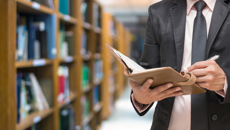 Businessman writing the note book on the Abstract blurred photo of library background