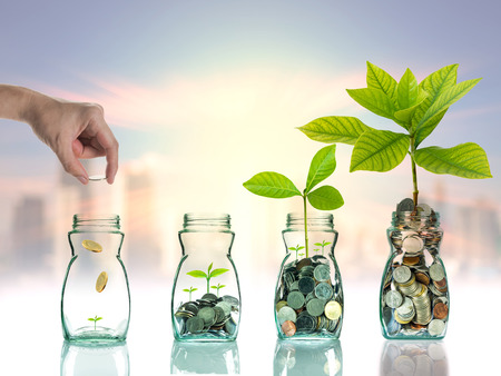 Hand putting mix coins and seed in clear bottle on cityscape photo blurred cityscape ,Business investment growth concept
