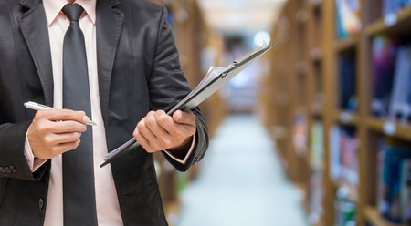 Businessman writing the file pad on the Abstract blurred photo of library background