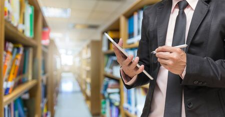 Businessman using the tablet on the Abstract blurred photo of library background