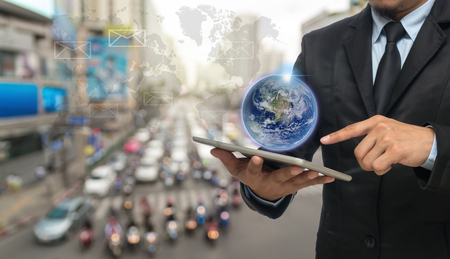 Businessman using the smart phone with earth and world map on abstract Blurred photo of traffic jam with rush hour, Elements of this image furnished by NASA