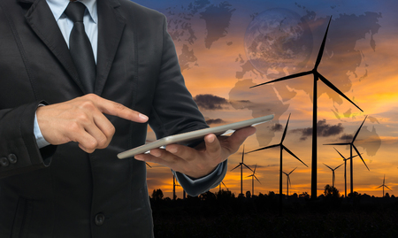 Businessman using the tablet on Wind turbine power generator at twilight time,Elements of this image furnished by NASA.