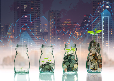 Mix coins and seed in clear bottle on trading graph with cityscape background,Business investment growth concept