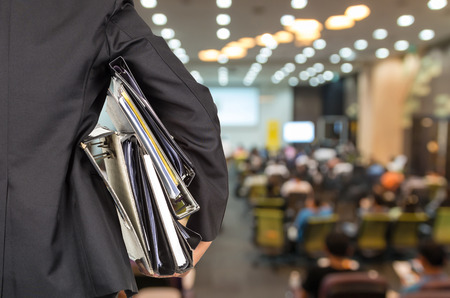 Foto de Businessman is holding many document folders on Abstract blurred photo of conference hall or seminar room with attendee background, back side, business busy concept - Imagen libre de derechos