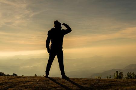 Photo pour silhouette of a man who looking over the mountains landscape - image libre de droit