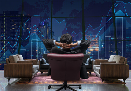 Foto de Back side of sitting businessman who is looking at Trading graph on the cityscape at night background,lobby sofa from dicut and retouch each elements, Business financial and investment concept - Imagen libre de derechos
