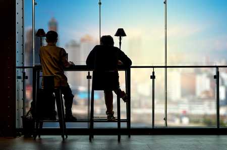 Silhouette of Man works at the workplace beside the windows on the photo blurred of cityscape building background, business workplace concept