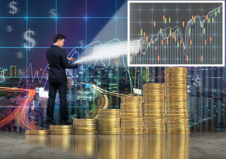 Asian Businessman standing over the stack of gold coins and using the tablet present the trading graph of Stock exchange market on trade graph background, Business trading and education concept