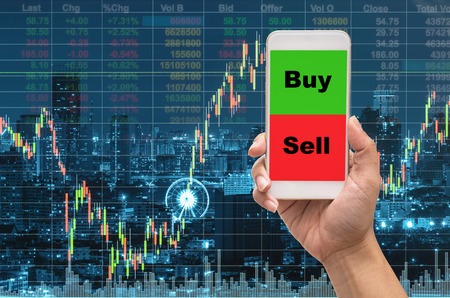 Female hand holding mobile phone touch screen showing buy and sell over the Stock market exchange information and Trading graph on the cityscape at night background,Business trading concept