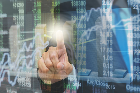 Businessman pointing the trading graph of stock market on the virtual screen on photo blurred of citysscape building background, Business stock market and trading concept