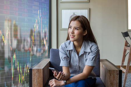 Happy asian businesswoman sitting on working space and looking the Stock market exchange information and Trading graph in the modern Office, Business financial concept