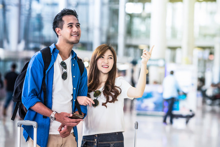 Asian couple traveler walking with suitcases in modern an airport, travel and transportation concept.motion style