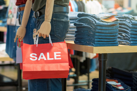 Part of male mannequin dressed in casual clothes holding the Sales paper shopping bag in the shopping department store for shopping, business fashion and advertisement concept
