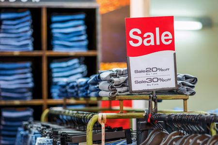 sale 80 off mock up advertise display frame setting over the stack of jeans and clothes line in the shopping department store for shopping, business fashion and advertisement concept